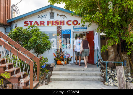 Couple entering Star Fish Co Seafood Market and Dockside Restaurant in the historic Florida fishing village of Cortez - Stock Photo