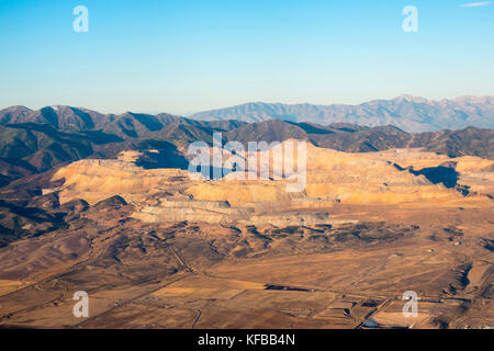 Bingham Canyon Kennecott Open Pit Copper Mine from the air in early morning light near Salt Lake City Utah - Stock Photo