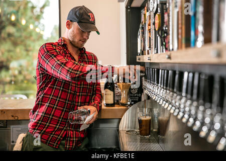 USA, Oregon, Bend, Pacific Pizza and Brew, bartender pouring pint - Stock Photo