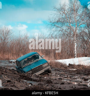 Stuck in dirt and abandoned car on a sunny spring day - Stock Photo