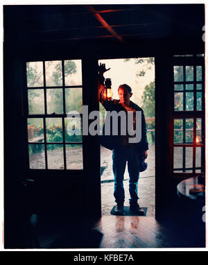 PANAMA, David, Guadalupe, Los Quetzales Lodge, man with a lantern in stays in a Swiss style chalet in the cloud - Stock Photo