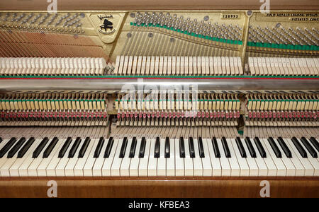 Upright piano stripped from upper front doors and fall showing keyboard and action mechanism. - Stock Photo