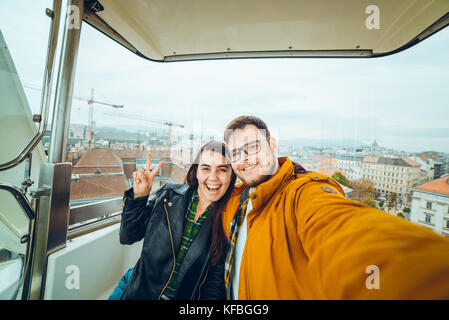 man with woman at ferris wheel taking a selfie - Stock Photo