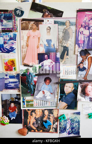 JAMAICA, Port Antonio. Family photos on a refrigerator door inside a local home. - Stock Photo