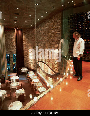 USA, Nevada, Chef Hubert Keller looking through glass wall of his Fleur De Lys Restaurant. - Stock Photo