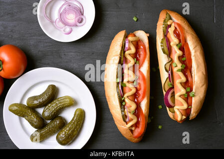 Homemade hot dogs with tomato, marinated cucumbers, onion on dark stone background. Top view - Stock Photo