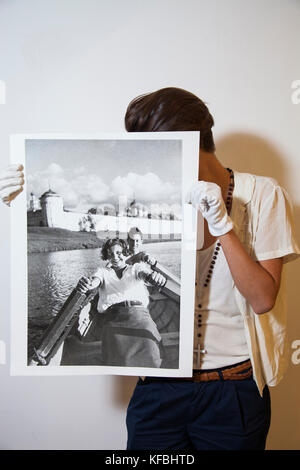 RUSSIA, Moscow. Gallerist showing a black and white photograph at the Lumiere Brothers Center for Photography. - Stock Photo