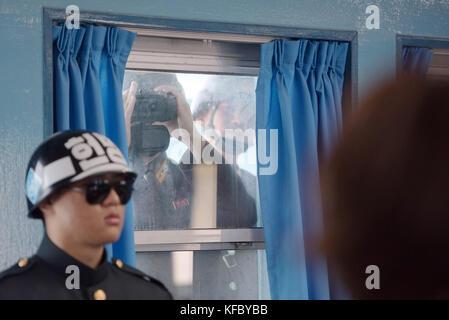 North Korean soldiers look through a window at U.S. Secretary of Defense Jim Mattis and South Korean Defense Minister - Stock Photo