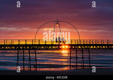 Southport, Merseyside, Sunset over Southport Pier. 27th October 2017. UK Weather.  A family take a stroll along - Stock Photo
