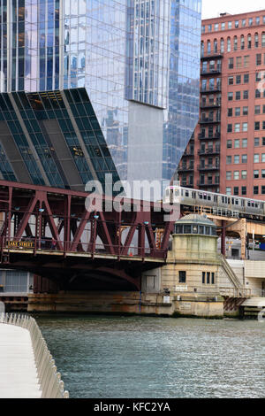 A pink line L train crosses the Chicago River at Lake Street in front of the cantilevered skyscraper at 150 N Riverside - Stock Photo