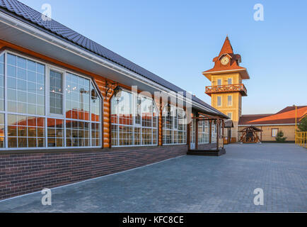 Cafe with a glass facade and a clock tower. - Stock Photo