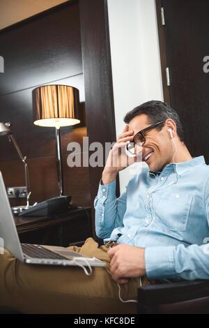 businessman in headphones using laptop - Stock Photo
