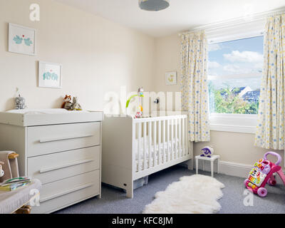 A modern, clean & tidy child's nursery room decorated in a contemporary style including a cot & changing table. - Stock Photo
