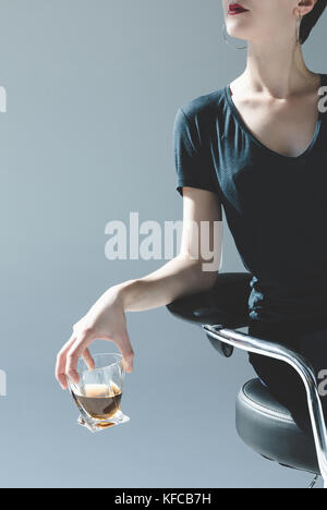 woman holding glass with whiskey - Stock Photo