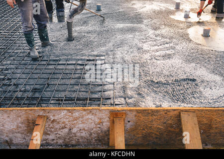 Concrete pouring during commercial concreting floors of buildings in construction - concrete slab - Stock Photo