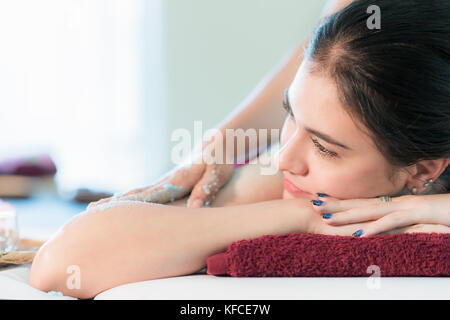 Young Asian woman receiving salt massage in spa salon, Hand putting salt scrub on female back, Spa concept - Stock Photo