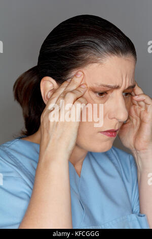 Female nurse or doctor suffering from an acute headache or migraine attack due too much stress and work - Stock Photo