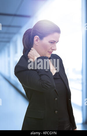 Middle aged woman with chronic pain syndrome fibromyalgia suffering from acute neckache - Stock Photo