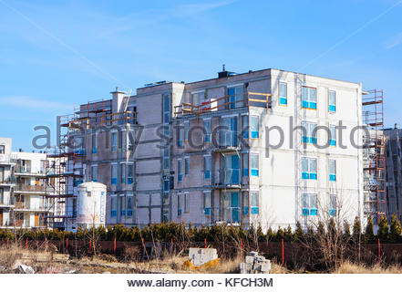 POZNAN, POLAND - FEBRUARY 27, 2016: Apartment building under construction on a sunny day - Stock Photo