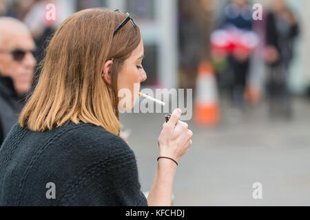Young woman lighting a cigarette in the UK. Unhealthy lifestyle. - Stock Photo