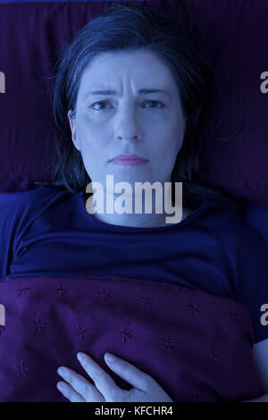 Middle aged woman lying awake in her bed at night, worrying because of an uncomfortable pressure in her chest and - Stock Photo