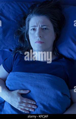 Middle aged woman lying awake in her bed at night because of insomnia, stress, fears, nightmares or restless leg - Stock Photo