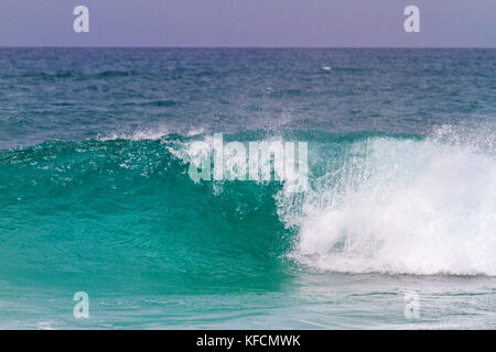 turquoise wave breaks up to the shore - Stock Photo