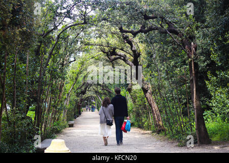 a couple walking in a path under the trees in boboli gardens, Florence,Italy - Stock Photo