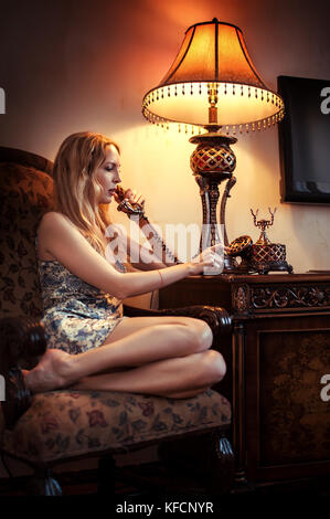 Young beautiful woman speaking by old vintage telephone with a dial-up dial and a tube on the wire. She sitting - Stock Photo