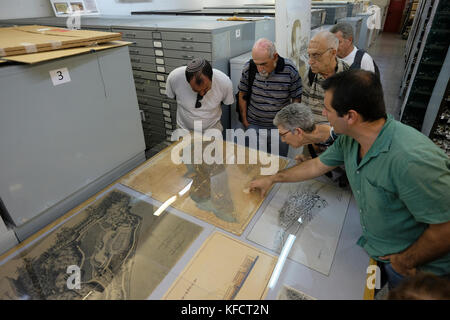 Israeli visitors inspecting original maps and plans of the Jewish state in its early years stored inside The Central - Stock Photo