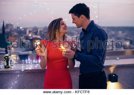 Young couple celebrate with champagne and sparklers in their hands - Stock Photo