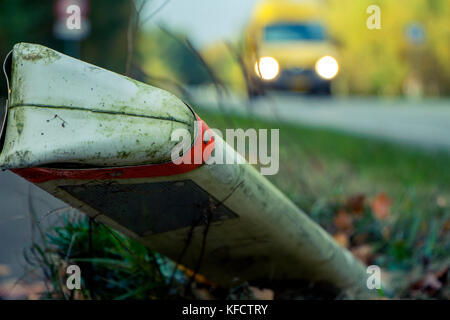 Road sign on grass and yellow car on road. - Stock Photo