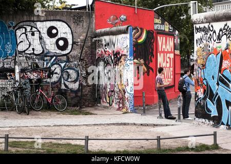 BERLIN-SEPTEMBER 26:Two unidentified people near the Berlin wall ,on September,26,2012,Berlin,Germany.