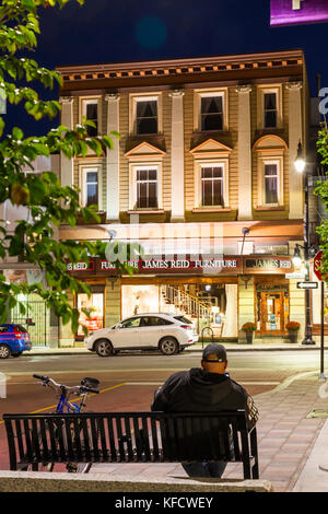 A man sitting on a bench at night with a historical building along Princess Street in Kingston, Ontario, Canada. - Stock Photo