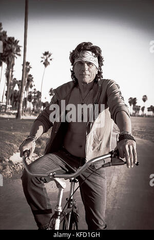 USA, Los Angeles, a man riding his bike down the Venice Boardwalk - Stock Photo