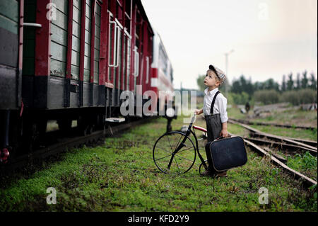 Four year old sad boy, dressed in retro style, stands at the train station with suitcase and bike - Stock Photo