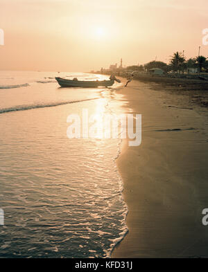 OMAN, Muscat, fisherman pulling boat at water's edge - Stock Photo
