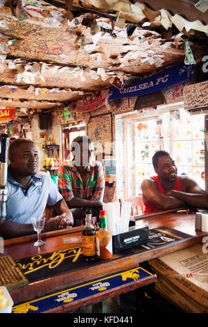 BERUMDA. Chef Marcus Samuelsson having a drink with the locals while watching a soccer game at the Swizzle Inn at - Stock Photo