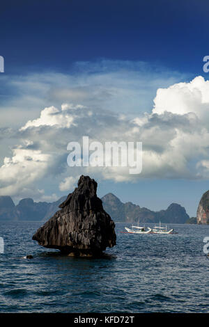 PHILIPPINES, Palawan, El Nido, view of surrounding rock formations and a fishing boat from Lagen Island Resort in - Stock Photo