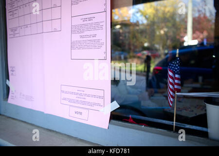 Small American flag sits behind a window of a polling station and an example ballot is posted on the outside, during - Stock Photo