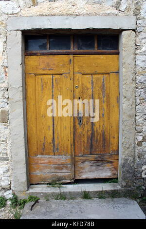 Old yellow wooden doors with small glass top windows and heavy stone frame put in traditional stone wall - Stock Photo