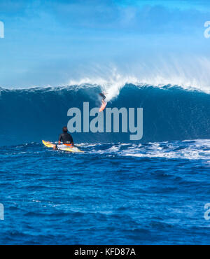 USA, HAWAII, Maui, Jaws, big wave surfers taking off on a wave at Peahi on the Northshore - Stock Photo