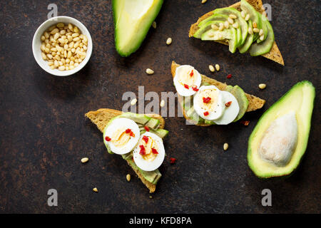 Sandwich avocado with fresh sliced avocado, egg poached and spices on a dark slate or stone background. Copy space. - Stock Photo