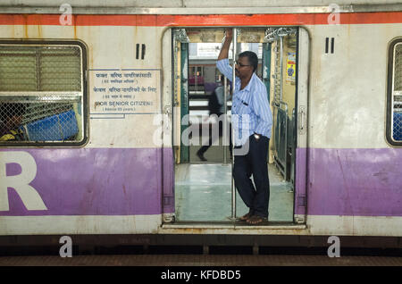A commuter on a train in Mumbai, India Stock Photo