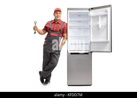 Full length portrait of a repairman holding a wrench and leaning against an empty fridge isolated on white background - Stock Photo