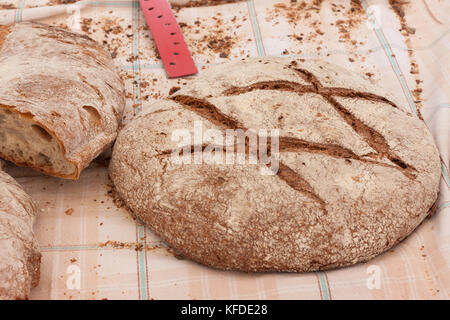 Freshly baked traditional Majorcan brown bread (pan moreno) on the table covered with tablecloth. Sineu market, - Stock Photo