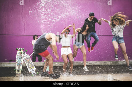 A group of young people jumping while being sprayed with water. - Stock Photo