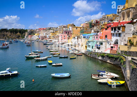 Harbor with moored boats, and colourful waterfront buildings on the hillside overlooking the waterfront. Procida, - Stock Photo