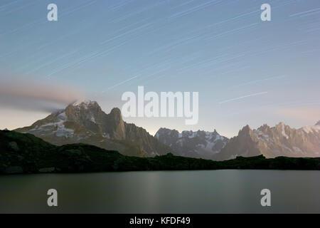 Star trail on the rocky peaks of Les drus and Aiguille Verte, Lacs De Cheserys, Chamonix, Haute Savoie, France - Stock Photo