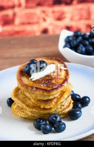 Stack of fresh homemade gluten free pancakes with blueberries, butter and syrup in front of brick wall background - Stock Photo